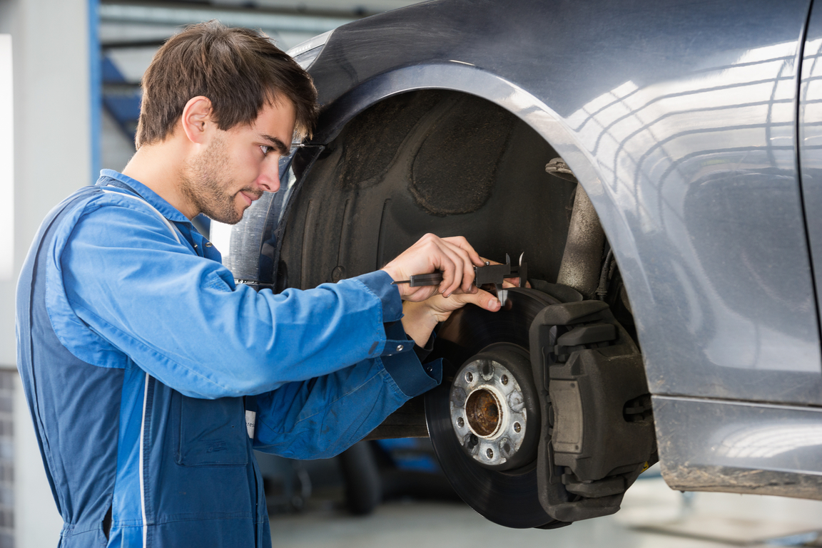 Car Brake Pads & Discs Being Checked By A Mechanic